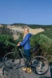 Lächelnde blonde Frau der Junge, die mit dem Fahrrad auf den Hintergrundbergen steht Lizenzfreies Stockfoto