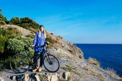 Lächelnde blonde Frau der Junge mit dem Fahrrad, das auf einem Felsen steht Lizenzfreie Stockbilder