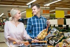 Lächelnde blonde Frau der Junge mit ihrem Ehemann, zum der Kartoffeln w zu kaufen Stockfoto