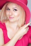 Lächelnde blonde Frau der Schönheitsmode im rosa Hut mit Make-up Stockfotografie