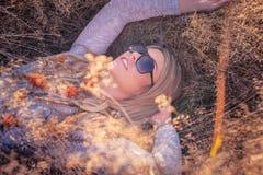 Lächelnde blonde Frau in der Sonnenbrille, die auf einem Gras liegt Stockfotografie