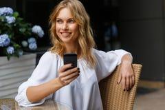 Lächelnde blonde Frau in der weißen Bluse mit Telefon in der Hand Lizenzfreie Stockfotografie