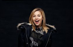 Lächelnde blonde Frau in der Winterjacke Lizenzfreies Stockfoto
