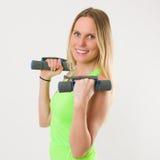 Lächelnde blonde Frau, die Übungen mit Dummköpfen tut Lizenzfreie Stockbilder