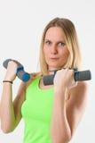 Lächelnde blonde Frau, die Übungen mit Dummköpfen tut Lizenzfreies Stockfoto