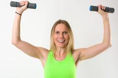 Lächelnde blonde Frau, die Übungen mit Dummköpfen tut Stockfoto