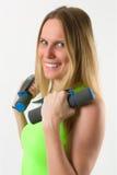 Lächelnde blonde Frau, die Übungen mit Dummköpfen tut Stockfotografie