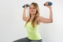 Lächelnde blonde Frau, die Übungen mit Dummköpfen tut Stockbild