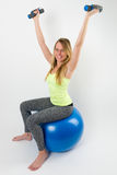 Lächelnde blonde Frau, die Übungen mit Dummköpfen tut Lizenzfreie Stockfotos