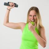 Lächelnde blonde Frau, die Übungen mit Dummköpfen und einem Apfel tut Stockfotos