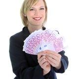 Lächelnde blonde Frau, die 500 Euroanmerkungen anhält Stockfoto