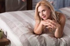 Lächelnde blonde Frau, die auf Bett liegt Stockfotos