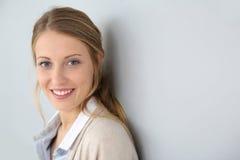 Lächelnde blonde Frau, die auf der Wand sich lehnt Lizenzfreie Stockfotos