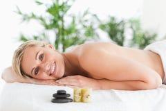 Lächelnde blonde Frau, die auf einem Nichtstuer liegt Stockbilder