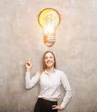 Lächelnde blonde Frau, die auf glänzende Extraglühlampe zeigt Stockbilder