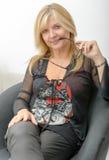 Lächelnde blonde Frau, die auf Lehnsessel sich entspannt Lizenzfreie Stockbilder