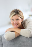 Lächelnde blonde Frau, die auf Sofa sitzt Stockfotografie