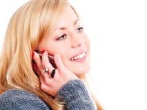 Lächelnde blonde Frau, die durch Telefon benennt Lizenzfreies Stockbild