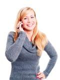 Lächelnde blonde Frau, die durch Telefon benennt Lizenzfreie Stockfotos