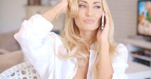 Lächelnde blonde Frau, die durch Telefon spricht Stockfotos