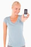 Lächelnde blonde Frau, die ein Telefon zeigt Stockfoto
