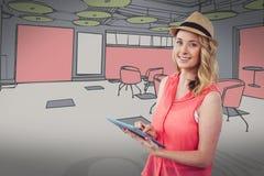 Lächelnde blonde Frau, die eine digitale Tablette mit einer farbigen Zeichnung auf Hintergrund verwendet Lizenzfreies Stockfoto