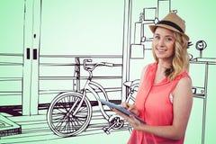 Lächelnde blonde Frau, die eine digitale Tablette mit einer grünen Zeichnung auf Hintergrund verwendet Stockfoto