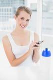 Lächelnde blonde Frau, die eine Textnachricht sendet Stockfoto