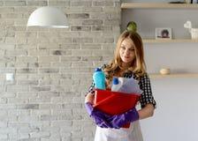 Lächelnde blonde Frau, die einen Eimer voll von den Reinigern hält Stockfotografie