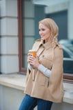 Lächelnde blonde Frau, die für einen Becher Kaffee pausiert Stockbilder
