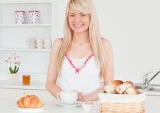 Lächelnde blonde Frau, die ihr Frühstück einnimmt Lizenzfreie Stockfotos