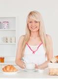 Lächelnde blonde Frau, die ihr Frühstück einnimmt Lizenzfreies Stockfoto