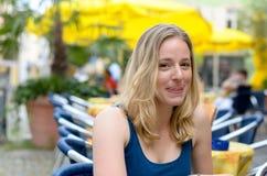 Lächelnde blonde Frau, die im Café sitzt Stockfotos