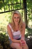Lächelnde blonde Frau, die im Schatten sich entspannt Stockfoto