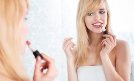 Lächelnde blonde Frau, die Lippenstift im Spiegel anwendet Lizenzfreie Stockfotos