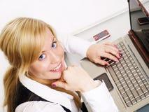 Lächelnde blonde Frau, die mit Computer arbeitet Stockbild