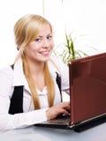Lächelnde blonde Frau, die mit Computer arbeitet Stockbilder