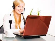 Lächelnde blonde Frau, die mit Computer arbeitet Lizenzfreie Stockbilder