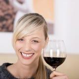 Lächelnde blonde Frau, die mit einem Glas Wein röstet Stockbild