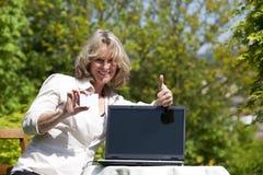 Lächelnde blonde Frau, die oben Daumen aufwirft Lizenzfreie Stockfotos