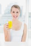 Lächelnde blonde Frau, die Orangensaft hält Stockfoto