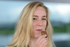 Lächelnde blonde Frau, die Schokolade isst Lizenzfreie Stockfotos