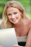 Lächelnde blonde Frau, die Tablette verwendet Lizenzfreie Stockfotografie