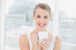 Lächelnde blonde Frau, die Tasse Kaffee hält Lizenzfreie Stockfotos