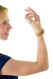 Lächelnde blonde Frau, die unterstützende Daumen-Klammer trägt Lizenzfreie Stockbilder