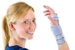 Lächelnde blonde Frau, die unterstützende Handgelenk-Klammer trägt Stockfotografie