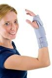 Lächelnde blonde Frau, die unterstützende Handgelenk-Klammer trägt Lizenzfreies Stockfoto