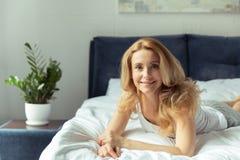 Lächelnde blonde Frau, die zu Hause auf Bett liegt Lizenzfreies Stockfoto