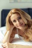 Lächelnde blonde Frau, die zu Hause auf Bett liegt Stockbild