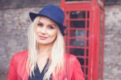 Lächelnde blonde Frau in einer roten Lederjacke Stockfoto